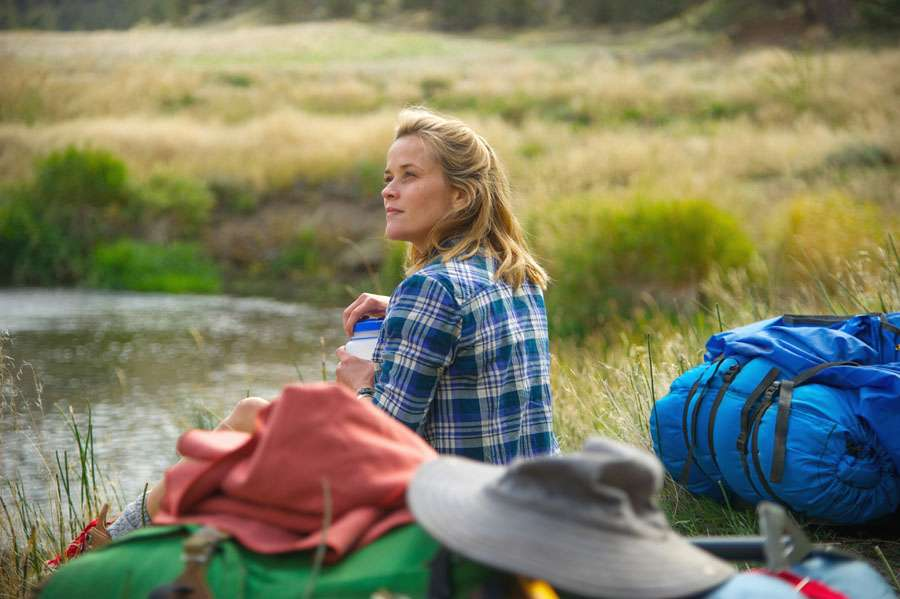 Reese Witherspoon in Wild (2014). Cheryl sits in the grass by the side of a small pond, her hiking gear strewn around beside her. She is holding a plastic container of water, and looks over her left shoulder towards the sky.